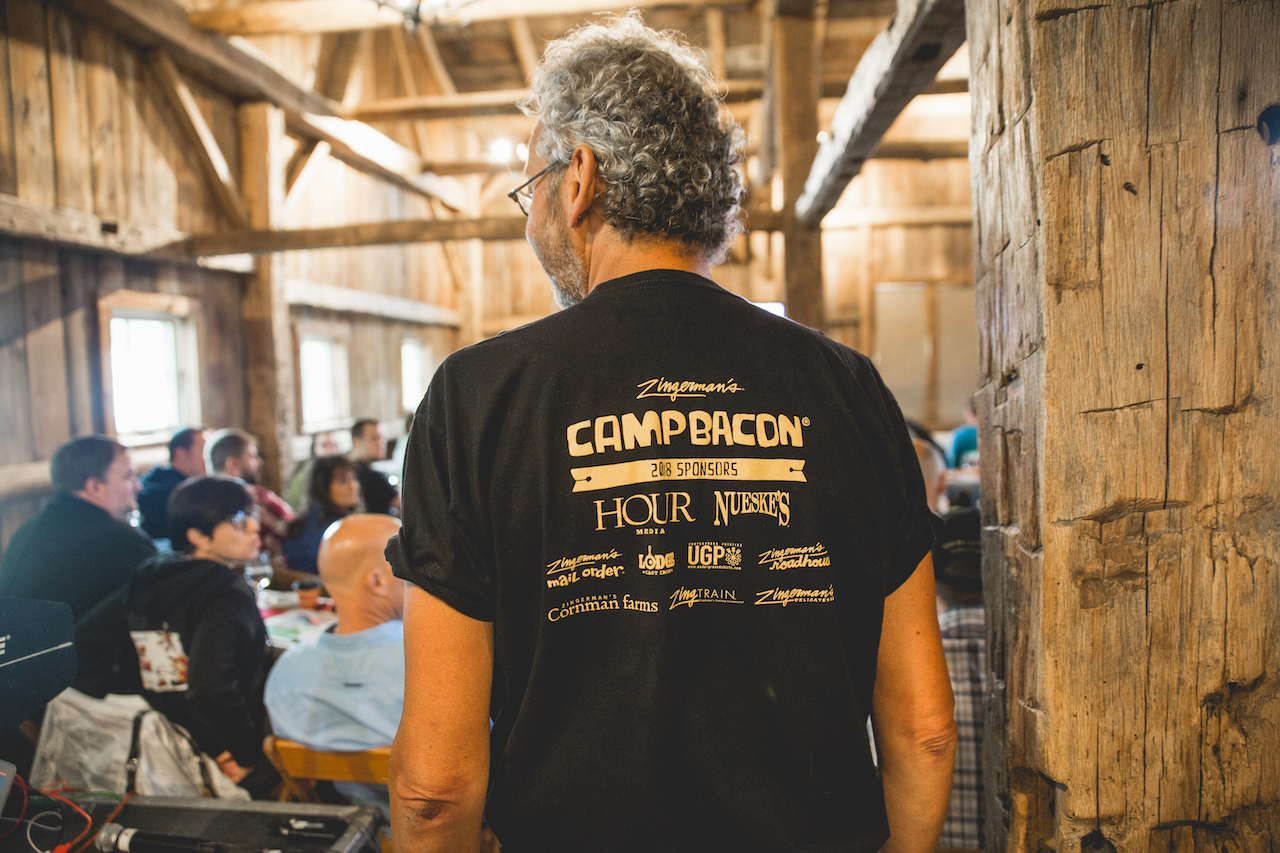 Zingerman's co-founder Ari Weinzweig is wearing a Camp Bacon t-shirt, on the back of which lists the 2018 sponsors.